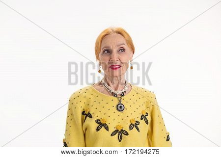 Old woman on white background. Thoughtful lady looking aside. Thoughts and plans.