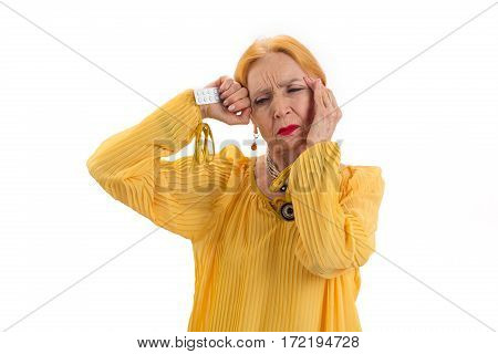 Isolated senior woman with pills. Upset lady touching her head. Take medicine against headache.