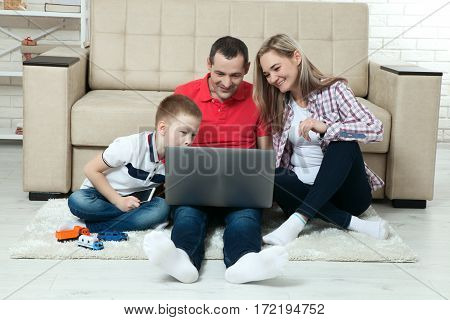Family having fun chating on internet with laptop. Family having fun chating on internet with laptop. Three people communicate on Skype at home in living room.