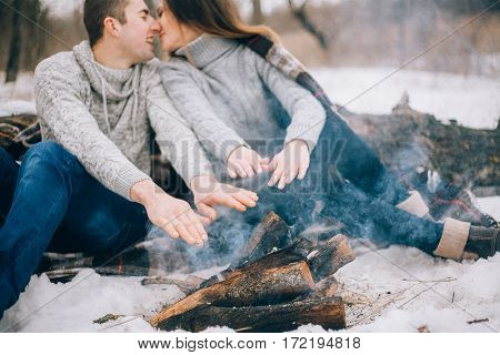 Young Woman And Man Warms Their Hands Over Bonfire During Winter Picnic.