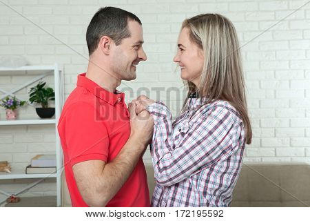 Young couple in love holding hands and looking each other close up of eyes.