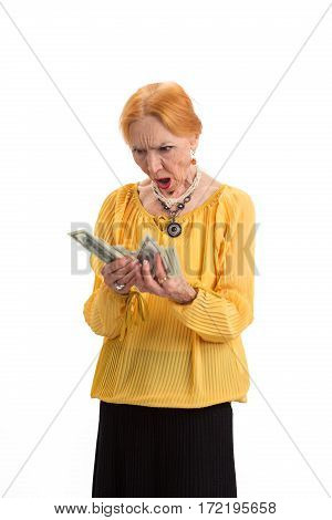 Elderly woman holding money isolated. Surprised lady looking at cash. Count the expenses.