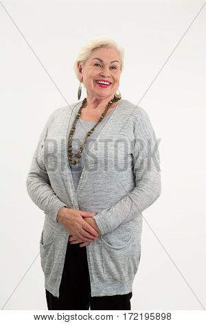 Senior woman standing and smiling. Happy lady on white background. How to smile better.