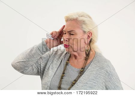 Old woman holding pills isolated. Senior lady having headache.