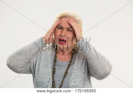 Senior woman having a headache. Lady holding her head isolated.
