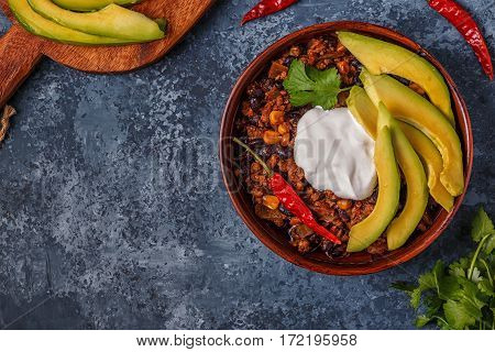 Chili con carne in bowl with avocado and sour cream, top view.