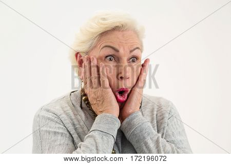 Surprised elderly lady isolated. Female with hands on face. See the unbelievable.