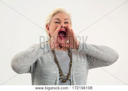 Senior lady shouting. Woman holding hands near mouth.