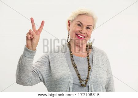 Senior woman showing peace gesture. Lady happily smiling. How to be friendly.