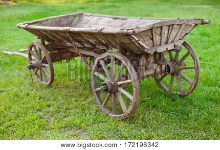 Old wooden cart on the green grass
