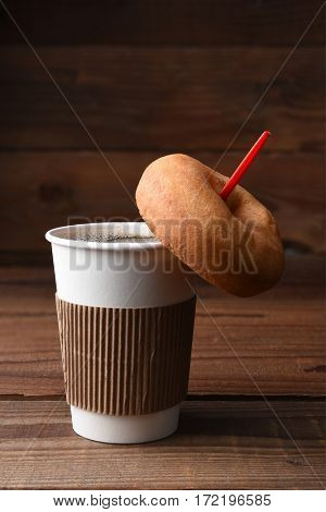 Closeup of a paper cup of hot fresh brewed coffee with a red spoon, A plain old fashioned donut is hanging on the spoon. Vertical format with copy space.