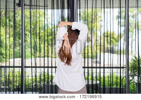 Woman stretching and standing while waking up in the morning