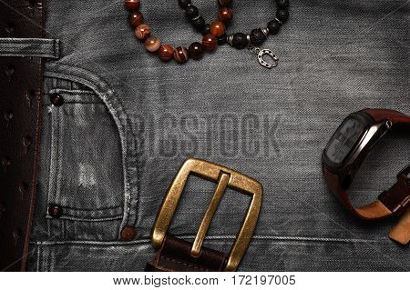 The objects of everyday life, men jeans, belt, watch, bracelets on hand. Flat top view. Men's fashion, casual outfits with accessories