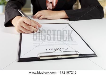 Hands of business woman signing the contract document with pen on desk - business concept.