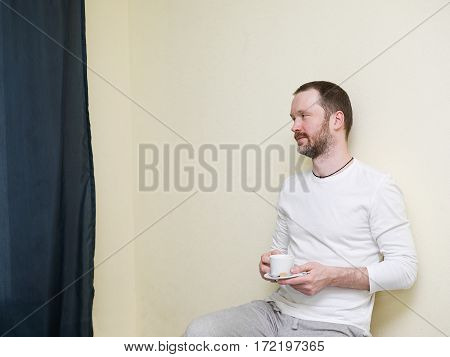 Man looking calm having coffee in an empty room sitting next to the curtain. Indoor cropped portrait