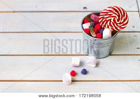 Colorful Candies In A Small Bucket On Light Wooden Background With Copy Space