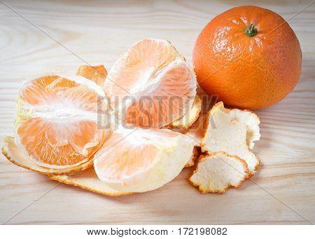 tangerines peeled tangerine and tangerine slices in a red plate on black background