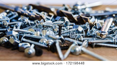 tapping screws made od steel, metal bolts, iron nuts, chrome screws, wood screw, stainless steel bolts and nuts on a wood background