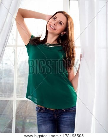 The beautiful girl with dark hair is by the window