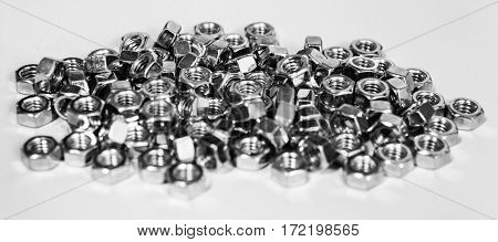 Close-up of stainless steel nuts, metal screw nuts, nuts made of chrome, nuts background, set of small and big iron nuts on white counter