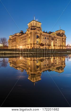 The famous Reichstag in Berlin at dawn reflects in the river Spree