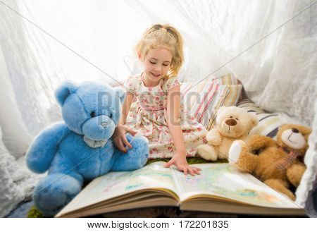 Little blonde child girl playing at home in her room with teddy bears.