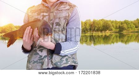 Fisherman With Carp In Hands On The Background Of The Lake.