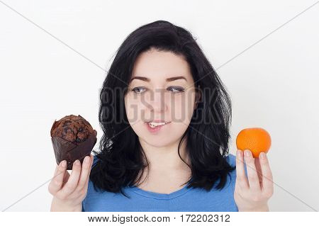 Young pretty woman making difficult choice between fruit and chocolate muffin. Dieting and weight loss concept.