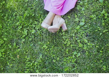 Feet of a bride on a green grass background. Happy bride in simple pink dress and stylish beige shoes sitting on a grass on wedding day. Summer wedding outdoors happy people copy space.