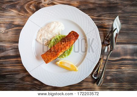 Grilled Salmon With Slice Of Lemon And White Sause On Wooden Background.