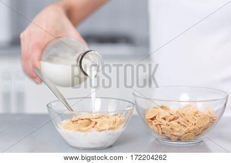 Crop of incognito female pouring milk in plate with oak flakes. Woman in white t-shirt cooking breakfast indoor in modern kitchen at morning.