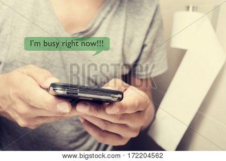closeup of a young caucasian man sitting in the toilet sending a message with his smartphone with the text I am busy right now