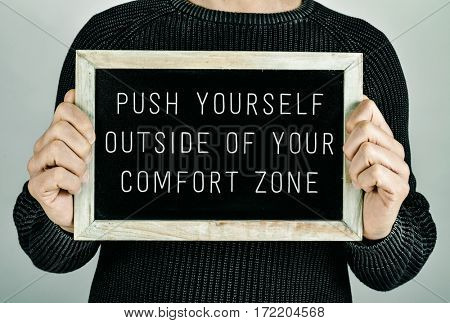 closeup of a young caucasian man holding a chalkboard in front of him with the text push yourself outside of your comfort zone written in it