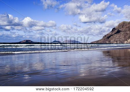 a view of the Famara Beach in Lanzarote, Canary Islands, Spain, with the Famara massif to the right and La Graciosa island in the background