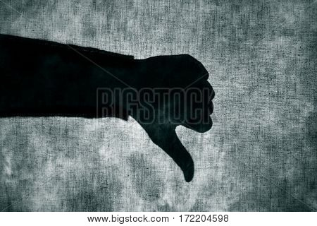 the shadow of a man giving a thumbs-down sign behind a gray fabric