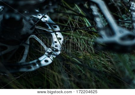 Disc Brakes Rotor Of Bicycle On Background Of Grass. Closeup Photo