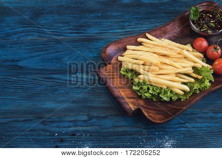 Fried potato on a blue wooden background