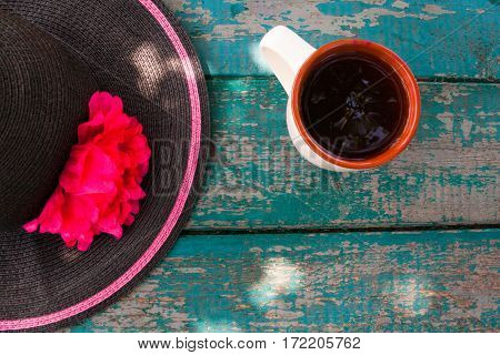 Elegant summer hat and cup of tea on the old wooden table.