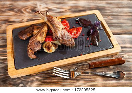 Roasted Lamb Ribs With Spices And Vegetables On Black Plate On Dark Wooden Background