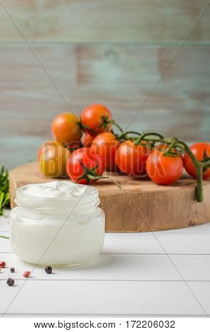 Organic cherry tomatoes with rosemary and cream cheese on rustic wooden table