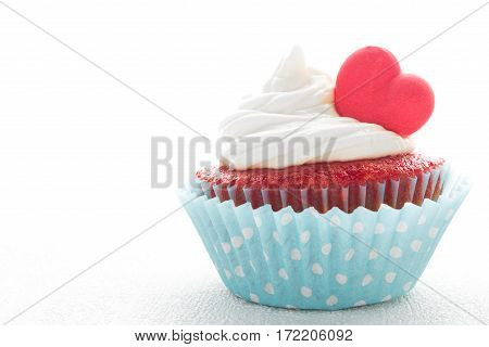 Red velvet heart cupcake with cream cheese frosting and a red heart for Valentine's Day. White background with copy space