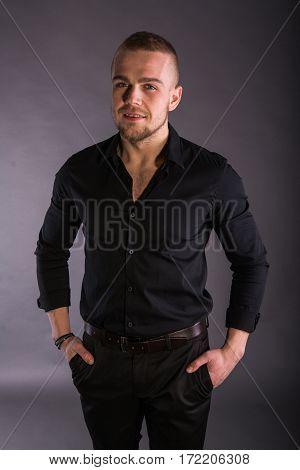 Close Up Smiling Young Businessman Wearing Black Shirt And Black Pants, Looking At The Camera Agains