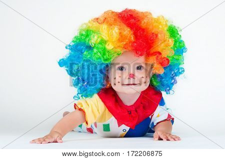 Children clown with a red nose multicolored wig in with balls. On a white background.