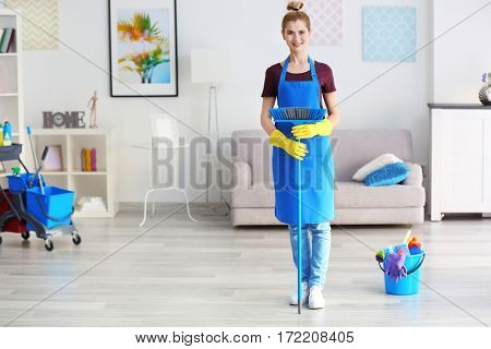 Pretty adult woman with floor brush at home