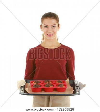 Woman in apron holding tray with chocolate muffins on white background