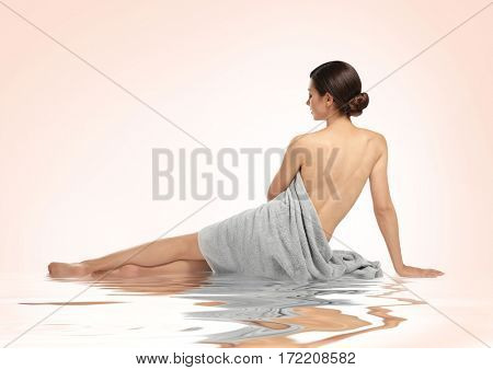 Young woman with towel sitting near water