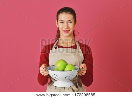 Woman holding apples in colander on color background