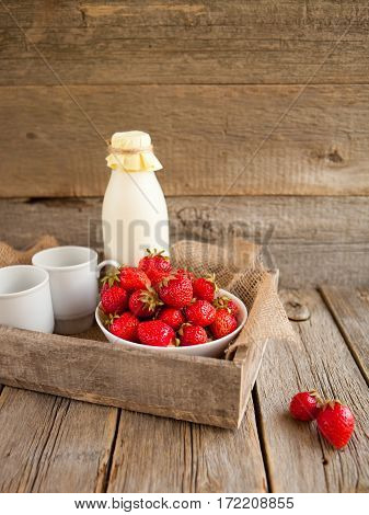 Fresh strawberries and milk in a bottle on a wooden background
