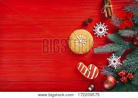 Composition of tasty gingerbread cookies and Christmas decor on red wooden background