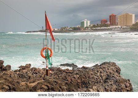 Red flag on beach of Punta Brava from beach in Puerto de la Cruz Tenerife Canary Islands Spain